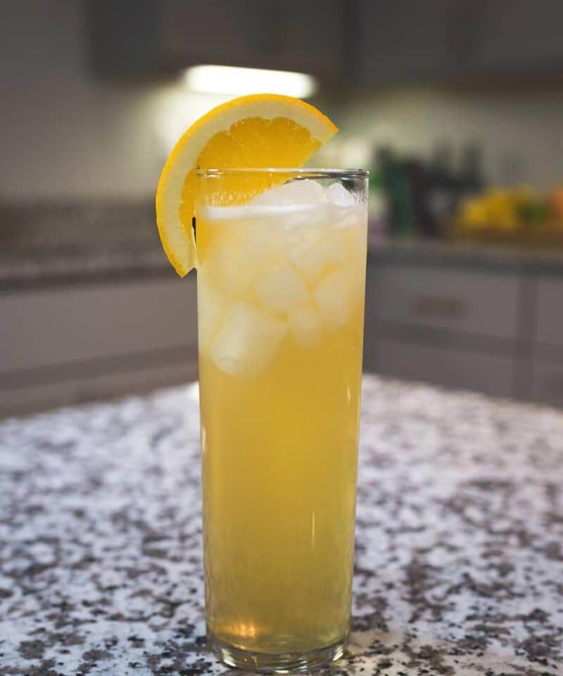 Super Bowl Shandy cocktail with lemon garnish, marble table