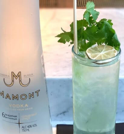 The Jolly Green Mamont, bottle and cocktail, marble table, cocktail napkin, featured image