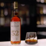 The Macallan 52 years old 2018, bottle and glass on bar table, featured image