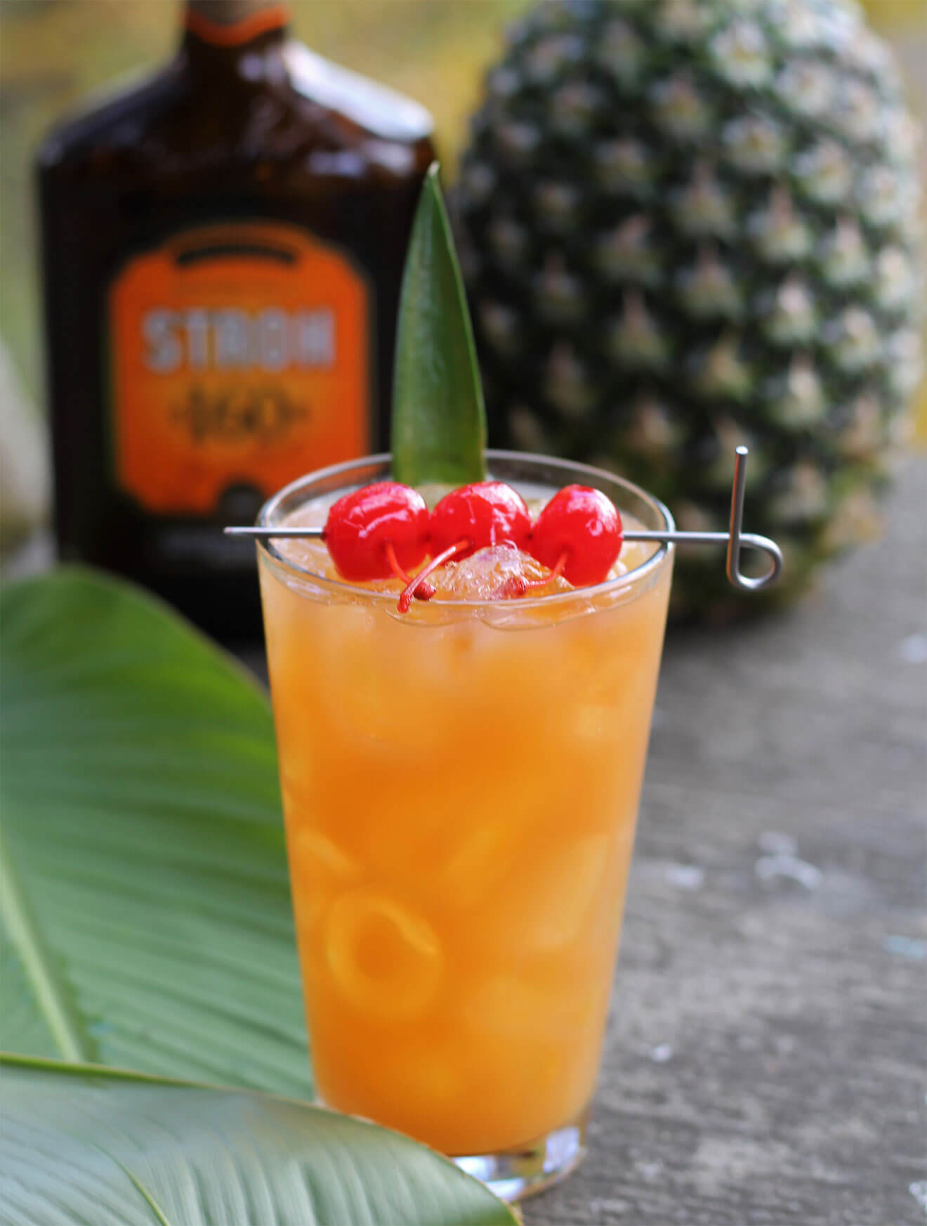 Three Dots and a Dash cocktail with cherry garnish, bottle and pineapple