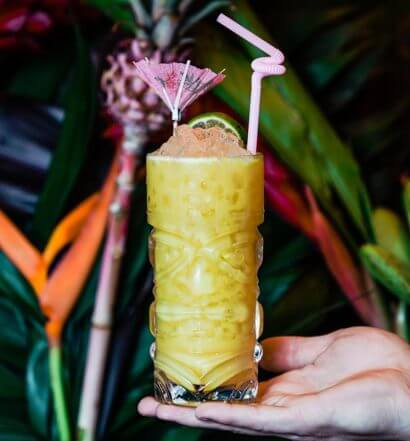 Yellowbelly cocktail in bartender's hand, tropical background, featured image