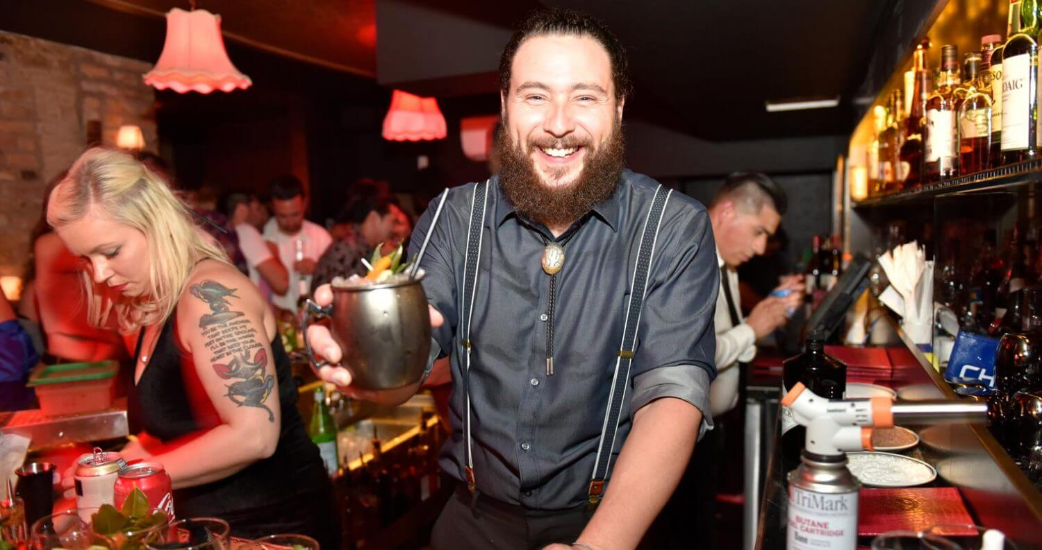 Justin Campbell, smiling behind the bar, featured image
