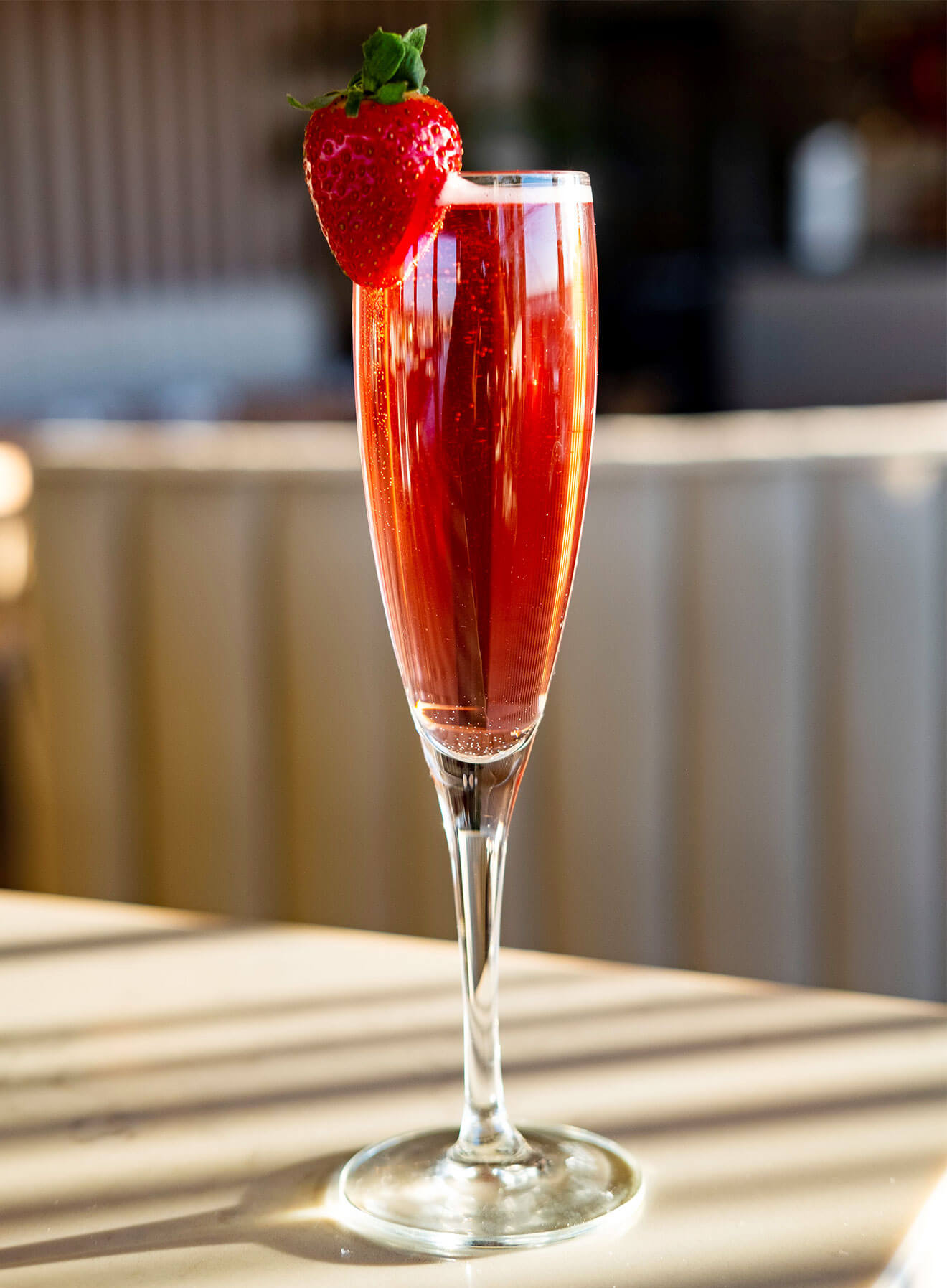 Los Amores, cocktail in champagne glass with strawberry garnish