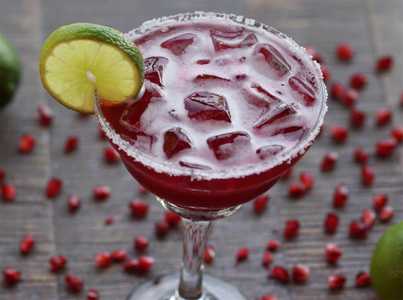 Pomegranate Margarita cocktail with lime wheel on ice
