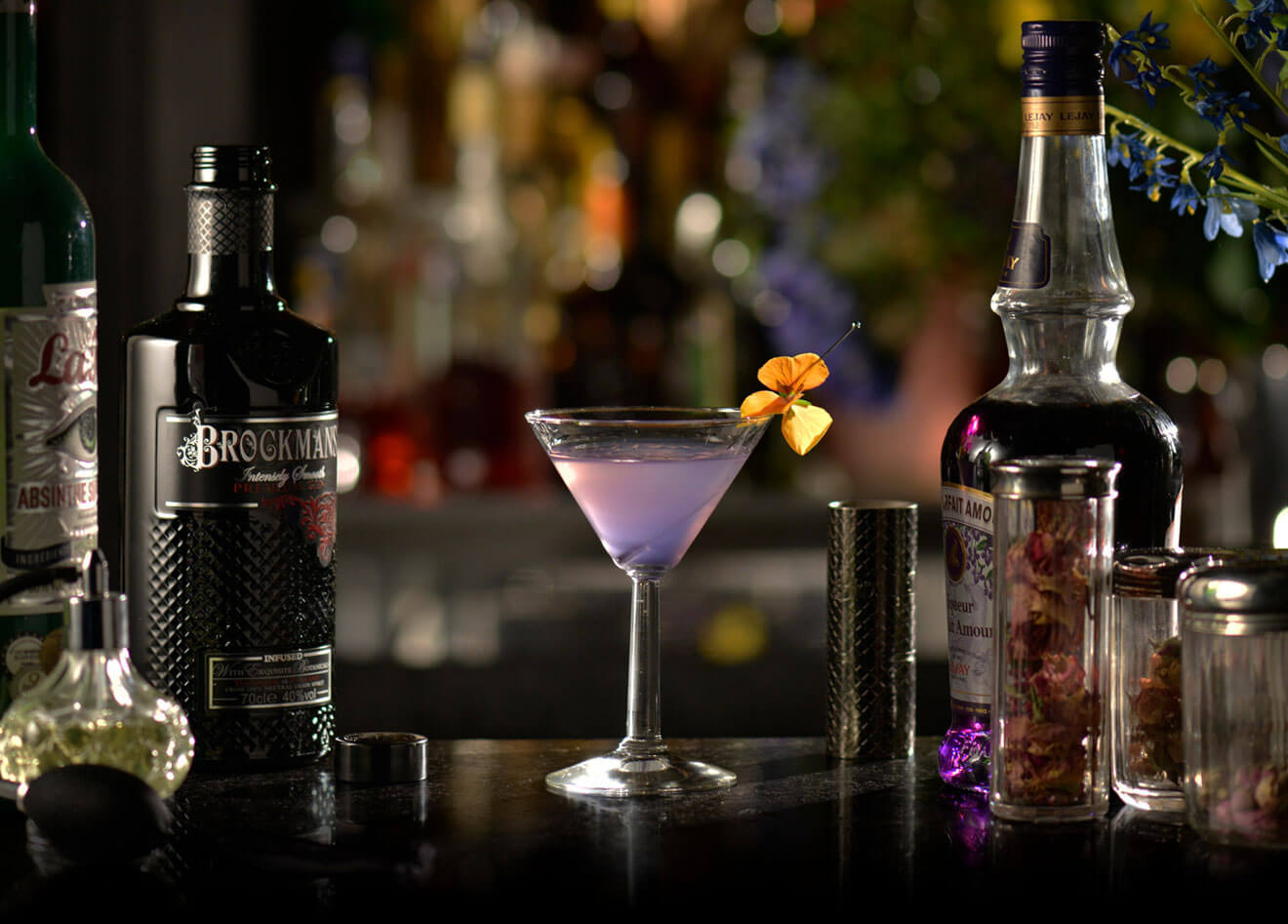 Ultra Violet, cocktail with garnishes, bottles on dark background