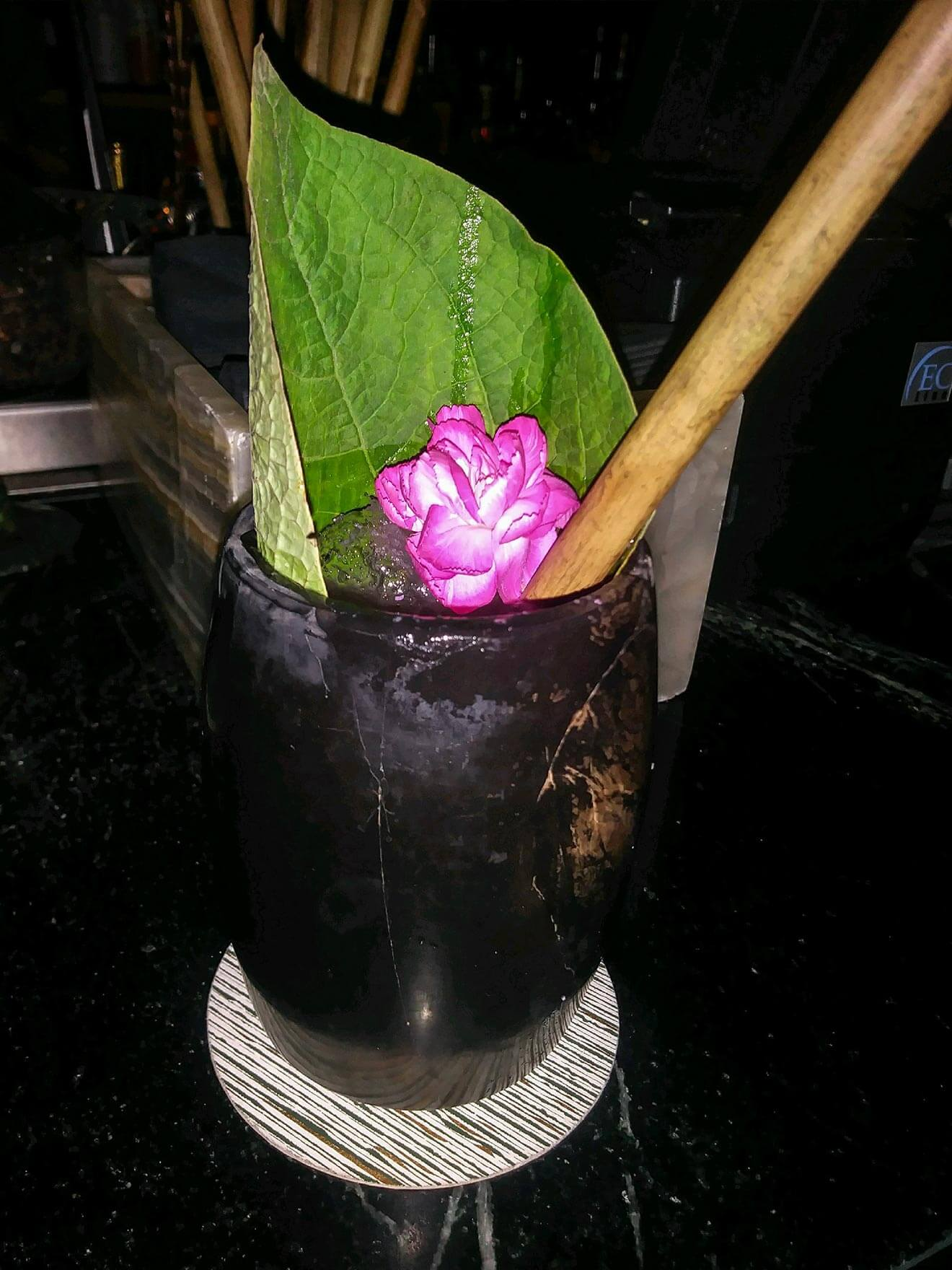 Xaman Cocktail with leaf and flower garnish