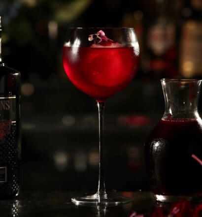 Purple Spring, cocktail with garnishes, dark background, featured image