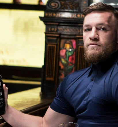 Connor McGregor's Irish Whiskey, holding bottle at bar, featured image