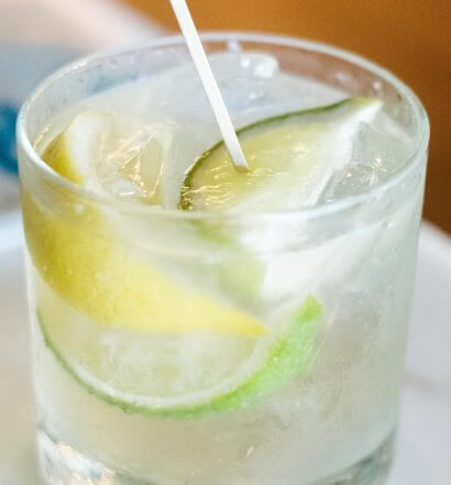 Mexican Bucha cocktail with lime wedges, featured image