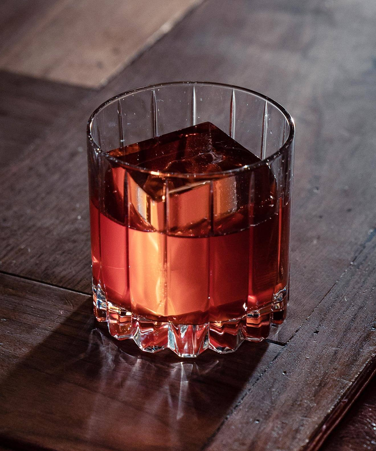 Mr Black Coffee Negroni, cocktail with large ice cube, wooden bartop