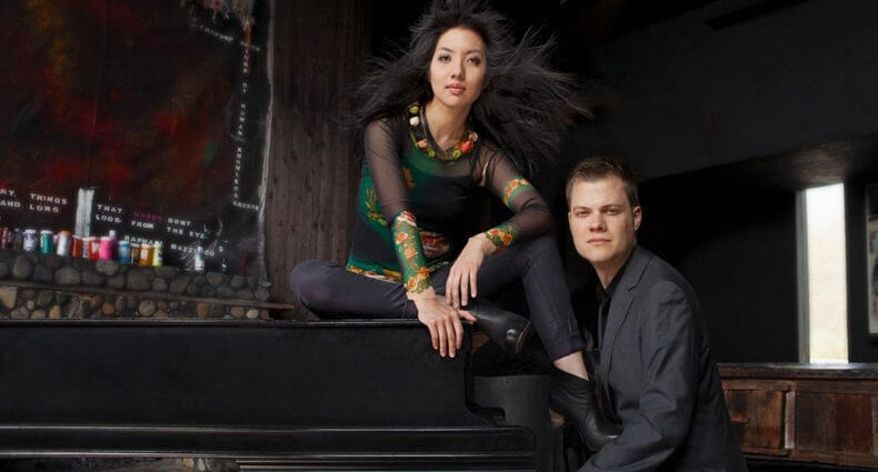 Anderson & Roe, piano duo posing with piano, featured image