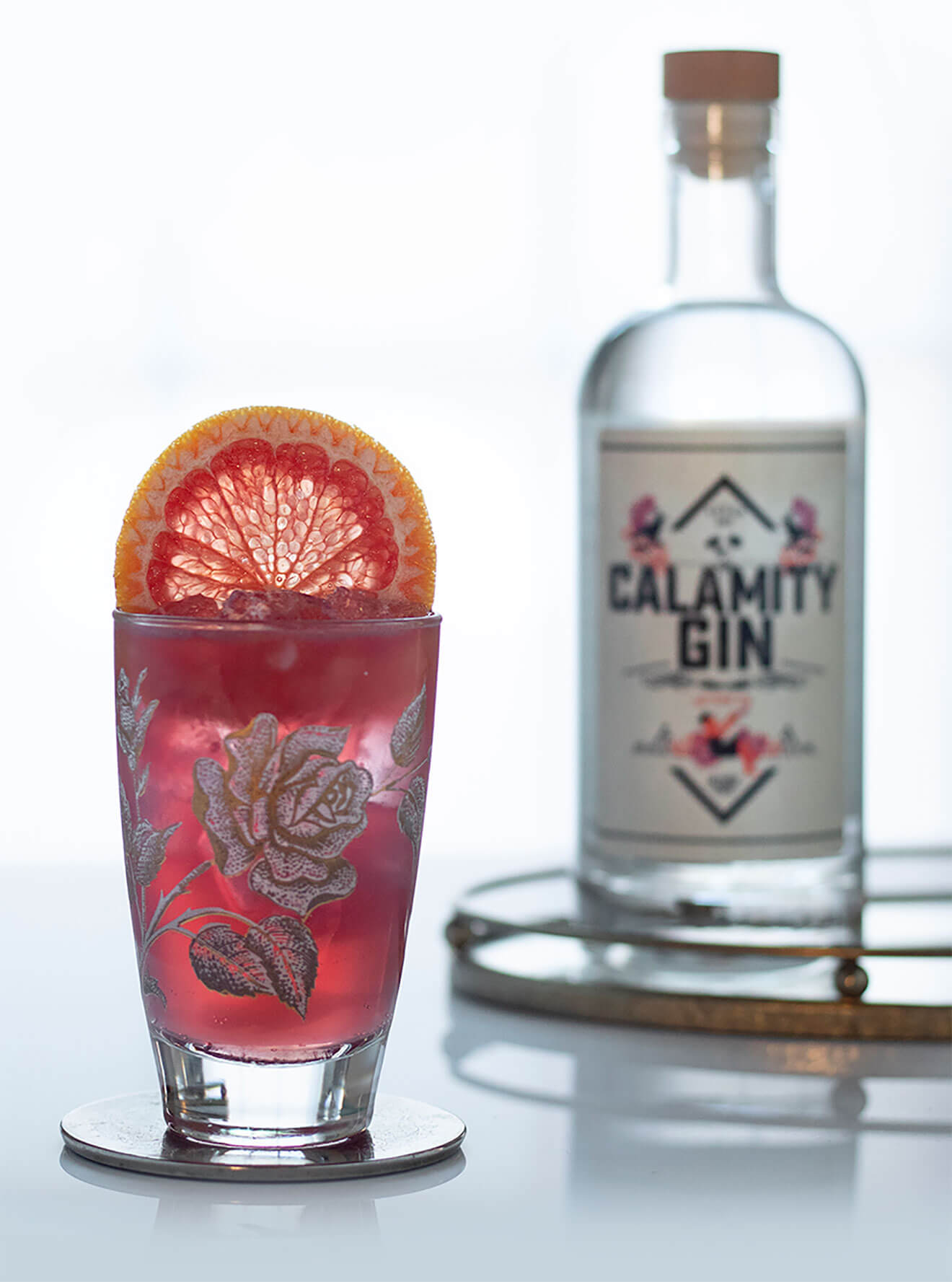 Calamity Garden G&T, cocktail with garnish and bottle on grey
