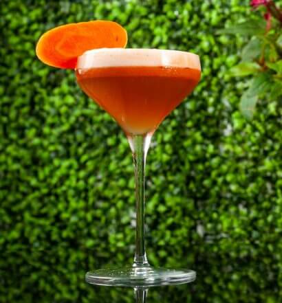 El Conejo Bueno, cocktail in garden with carrot garnish, featured image
