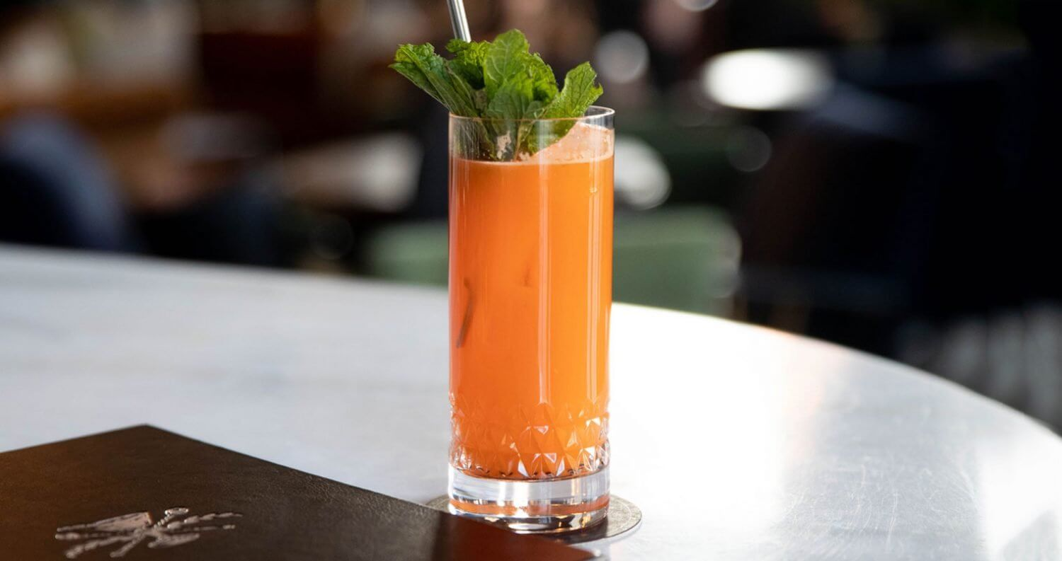 Nona's Harvest, cocktail with garnish on white table, featured image