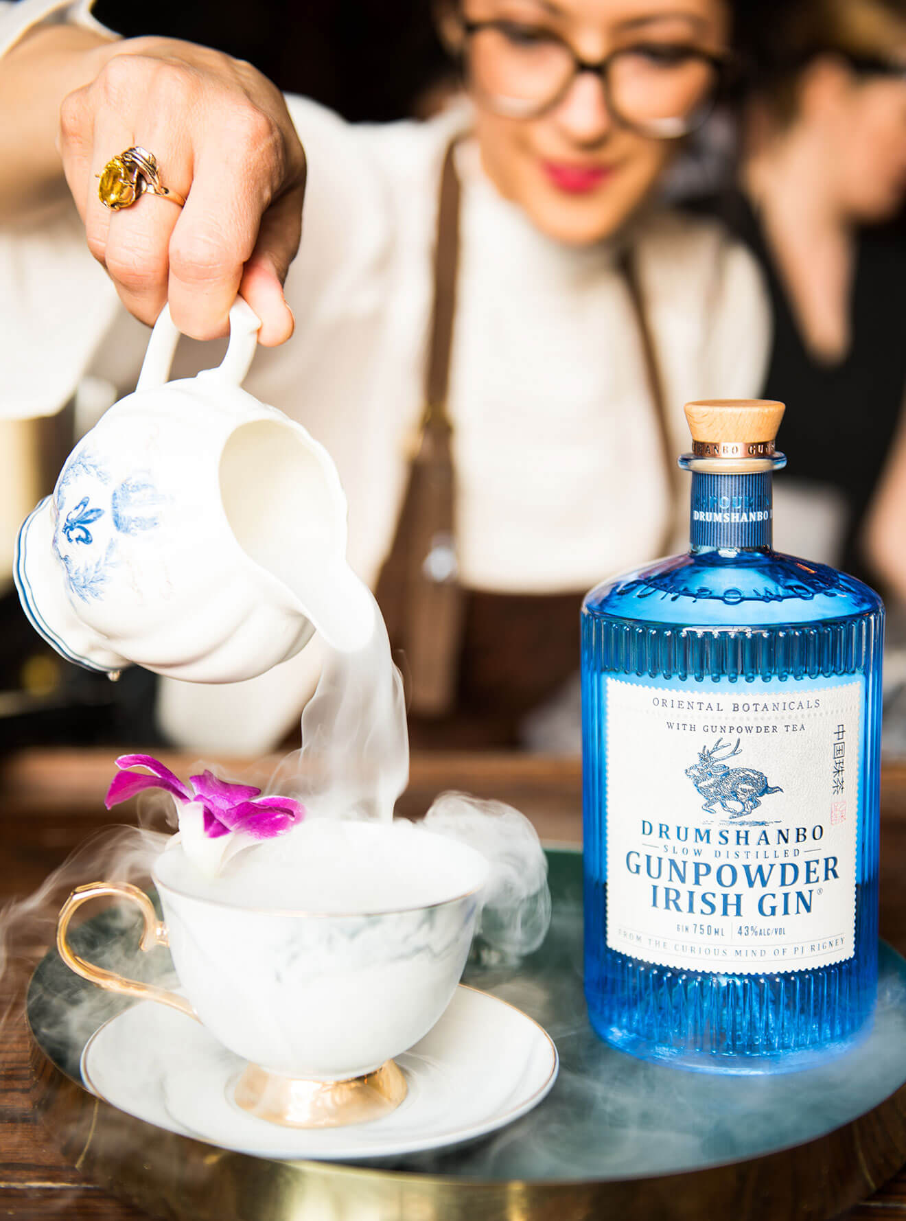 Smoking Gun cocktail being poured in a tea cup
