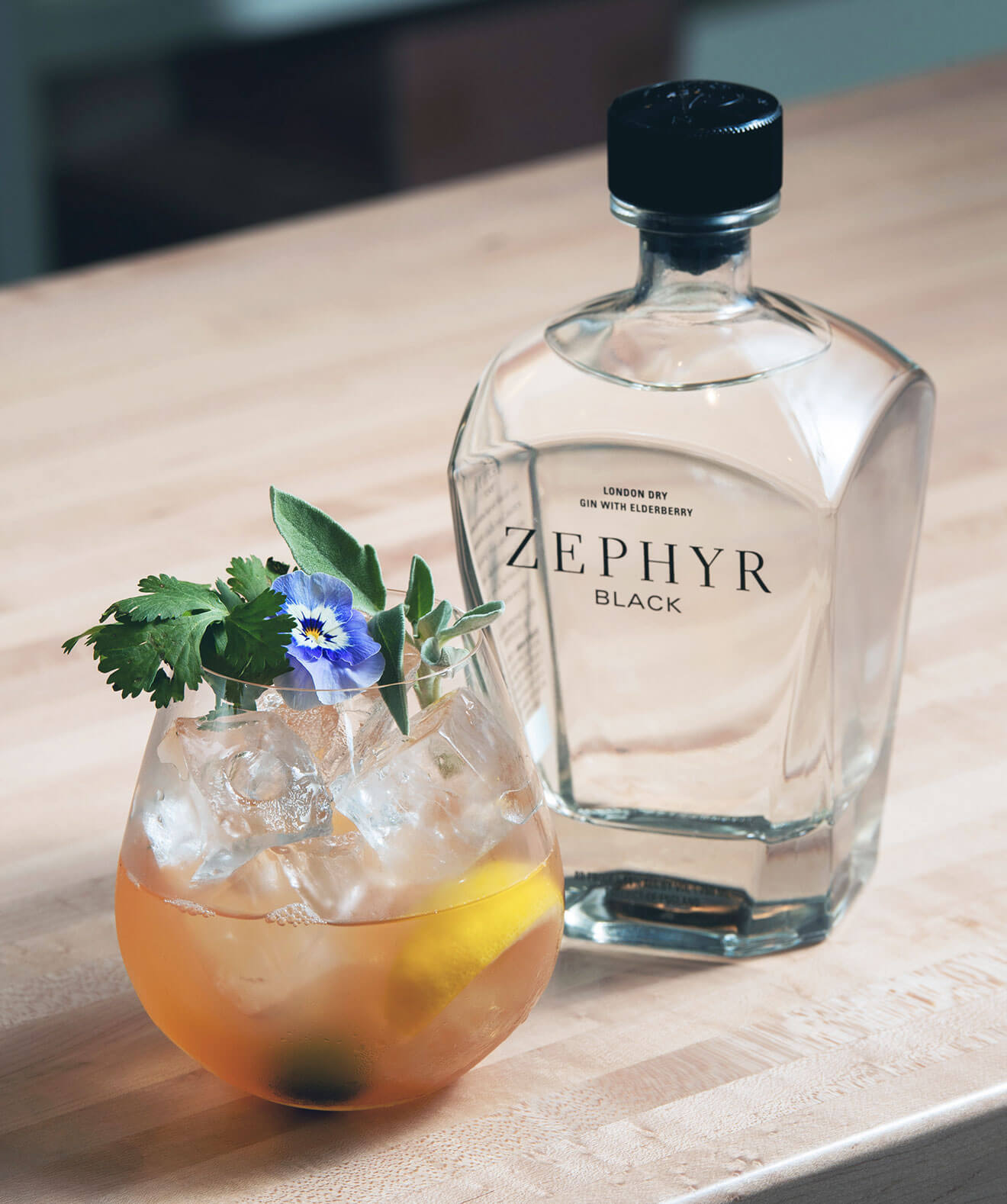 Zephyr Black Gin & Tonic, cocktail and bottle, wood table, angle overhead view