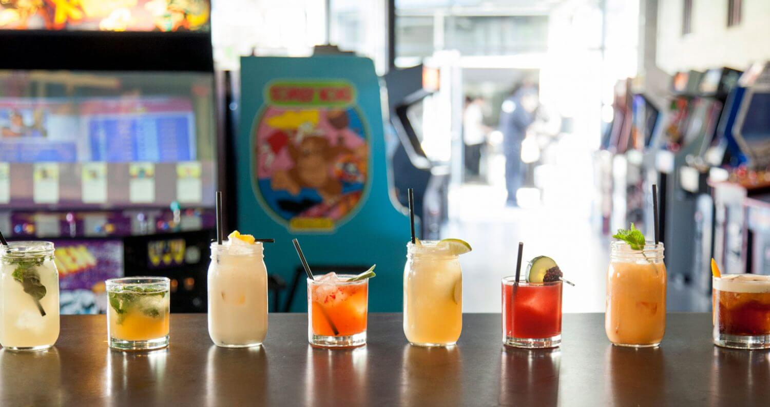 8 Awesome Arcade Bars, cocktails in a row, bar top in barcade