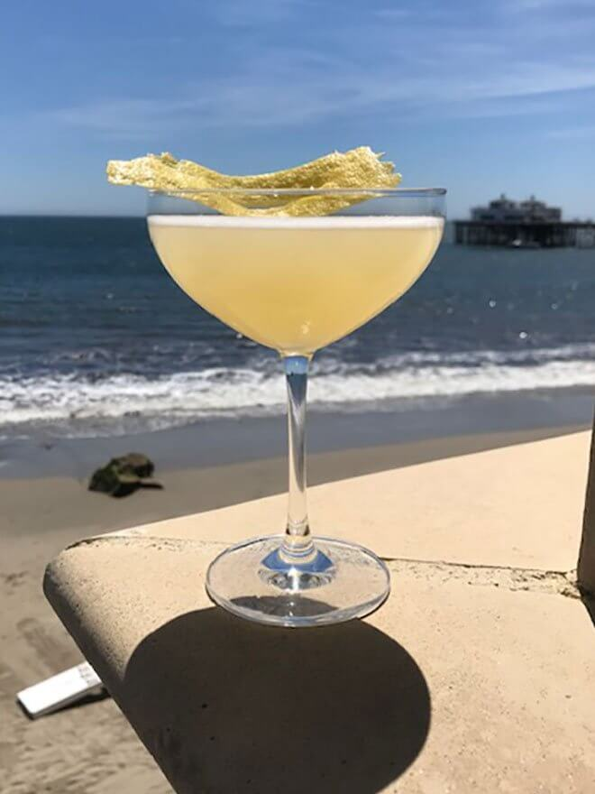 Bee's Knees 2019, cocktail with garnish, beach view in back