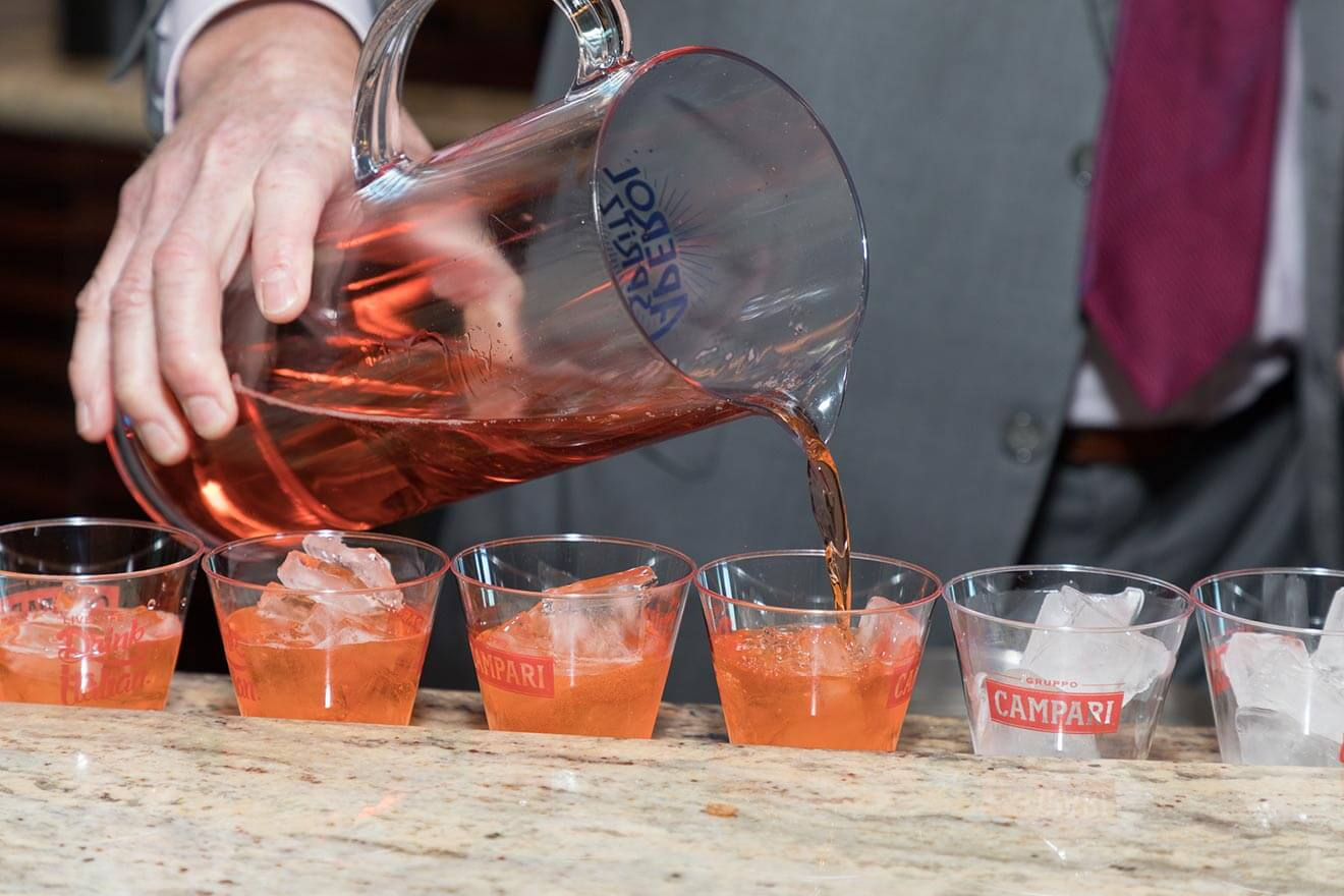 Aperol Spritz, cocktails in a row being mixed