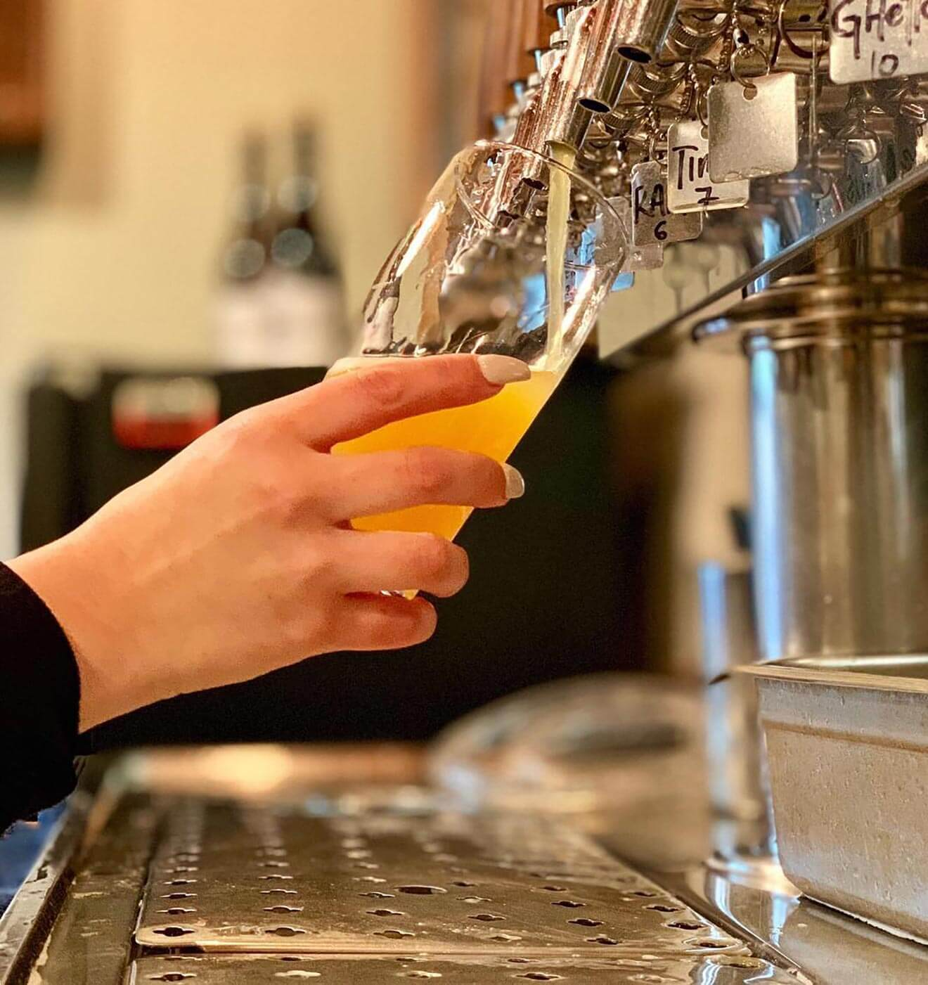 Monkish Brewing company, bartender pouring a draft