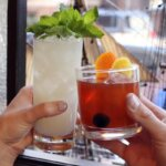The 6 Best Hotel Bars in Denver, two cocktails in a cheers, featured image