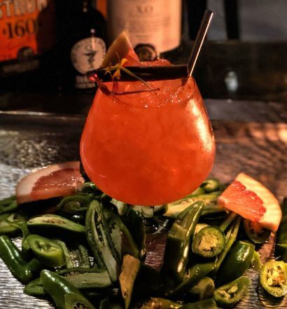 The Captain's Bride cocktail with pepper garnishes, and bottles in background, featured image