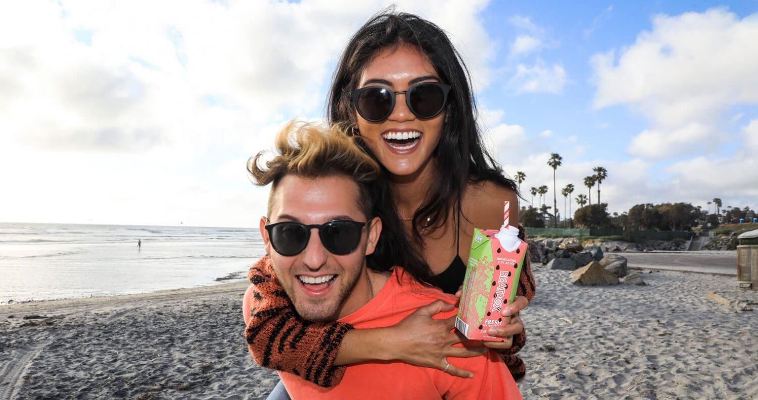 BeatBox Beverages, couple on beach, piggy back, featured image