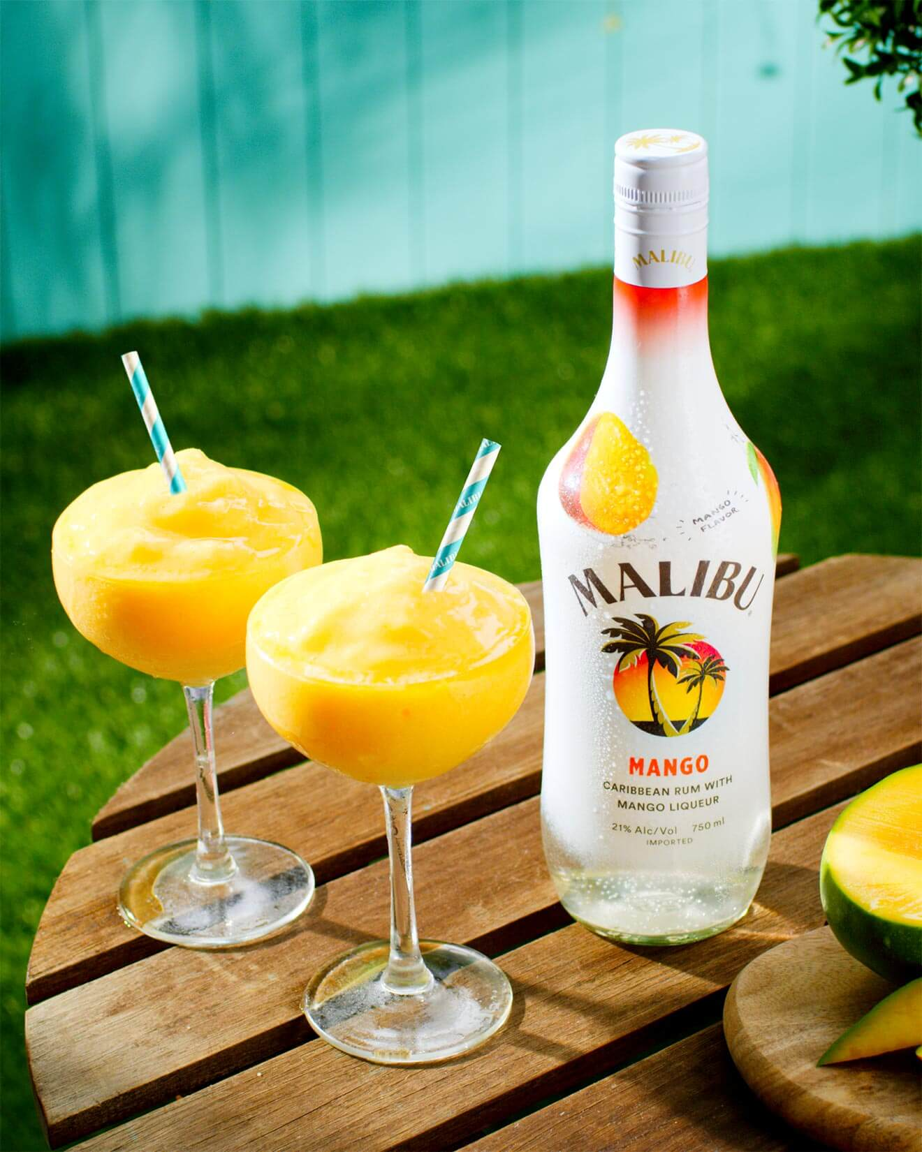 Malibu Mango Frozen Daiquiri, frozen cocktail with bottle, wooden round table