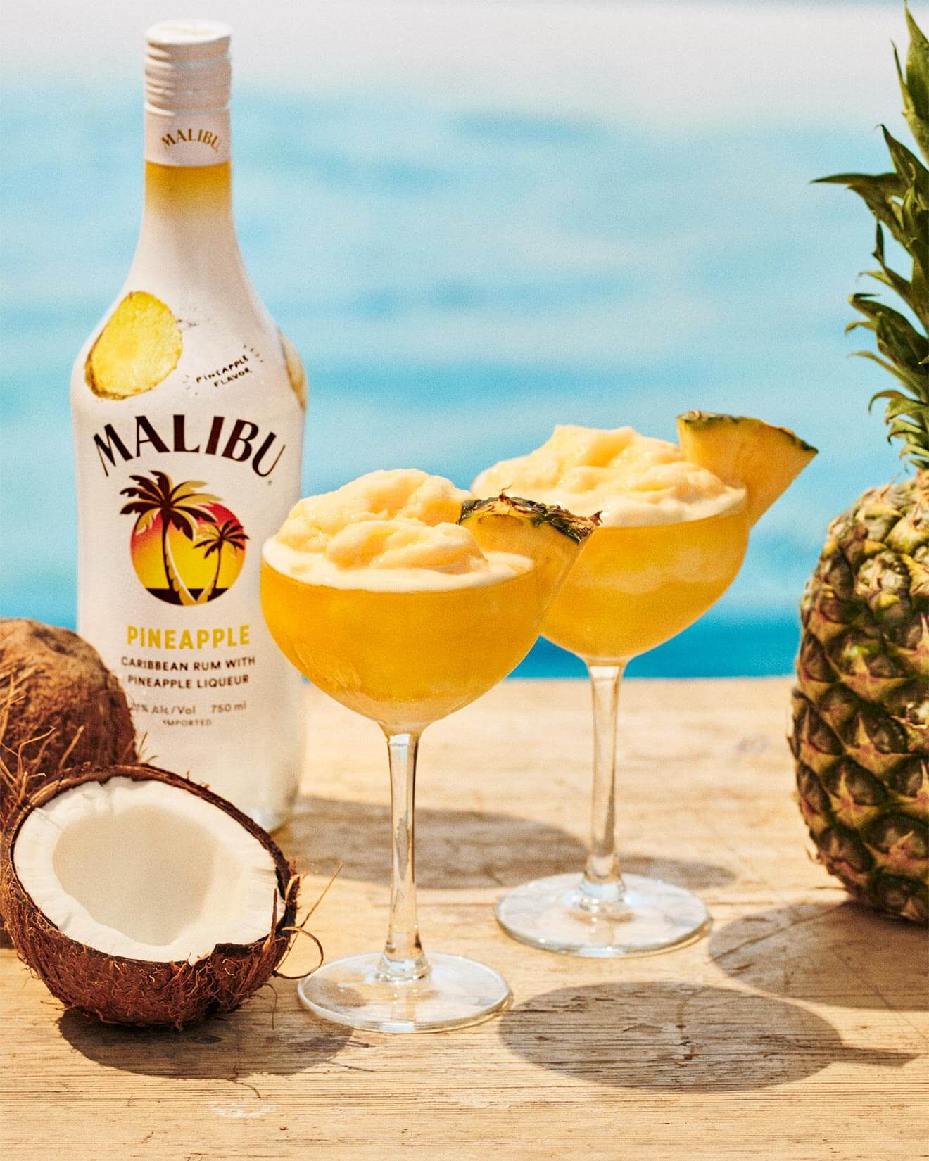 Malibu Pineapple Frozen Daiquiri, frozen cocktail with bottle, poolside table