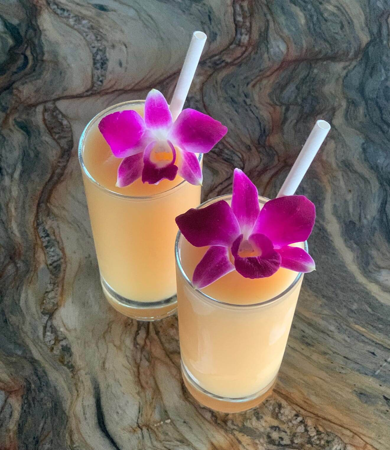 Tropic Like It's Hot, cocktails with edible purple flower garnish
