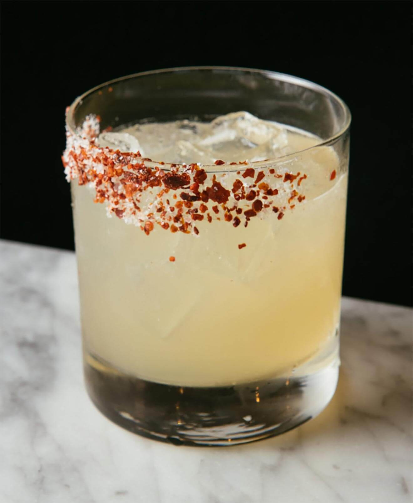 Dionysus Revival cocktail with salt garnish, marble table