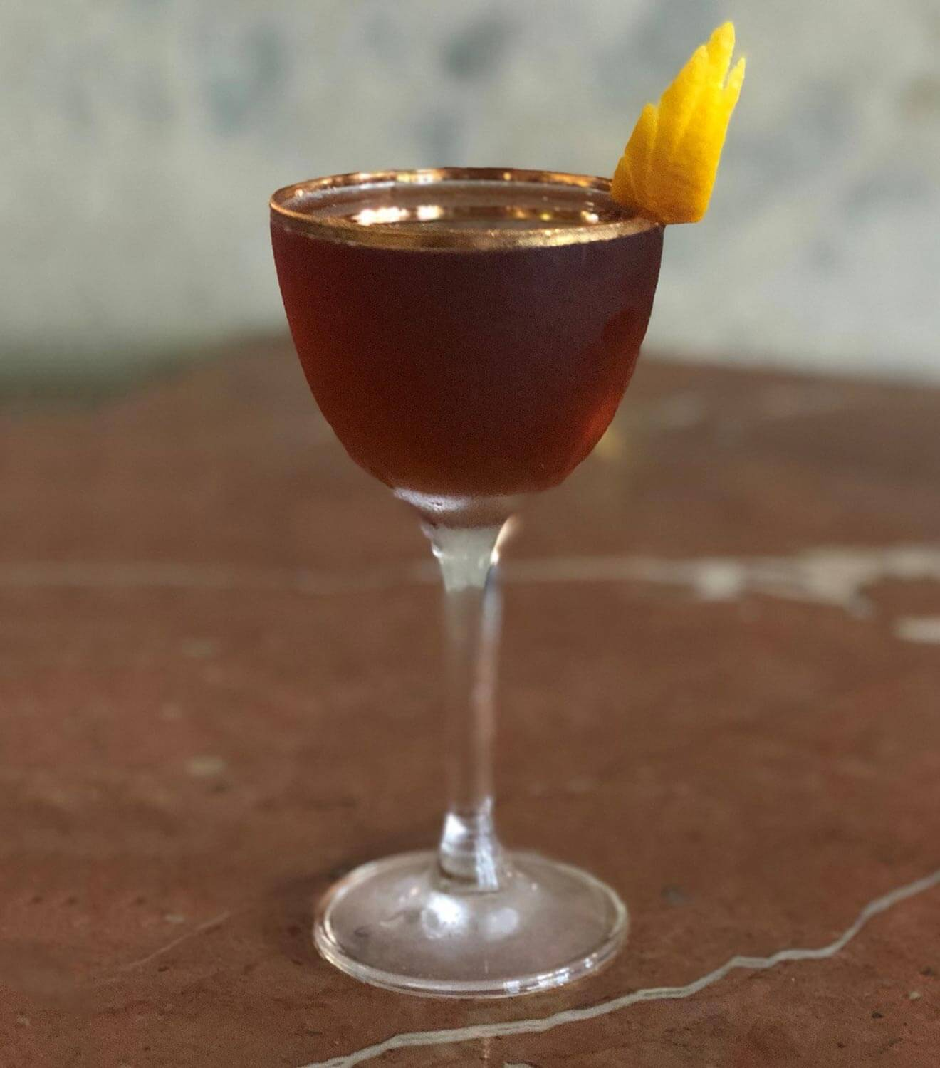 Sloe Ryder cocktail with lemon wing garnish
