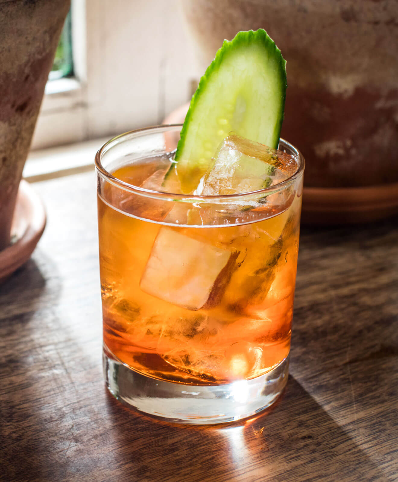 Red Cactus, cocktail on rocks with cucumber garnish