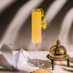 Airmail cocktail with garnishes on light shadowed back, featured image