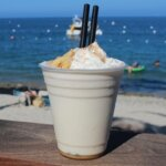 Buffalo Milk Cocktail, plastic cup and straws, beach background, featured image