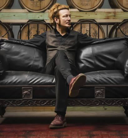 Tommy Brunett, sitting on leather couch, featured image