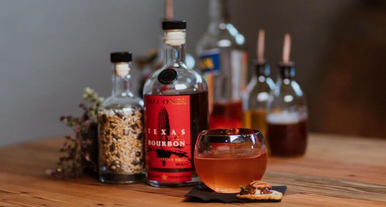 Upstairs Neighbor winning cocktail, with bottles and garnish, featured image