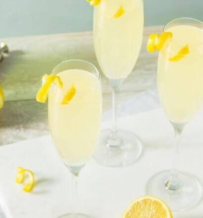 French 75 cocktails, with lemon garnish, tray and lemons, featured image
