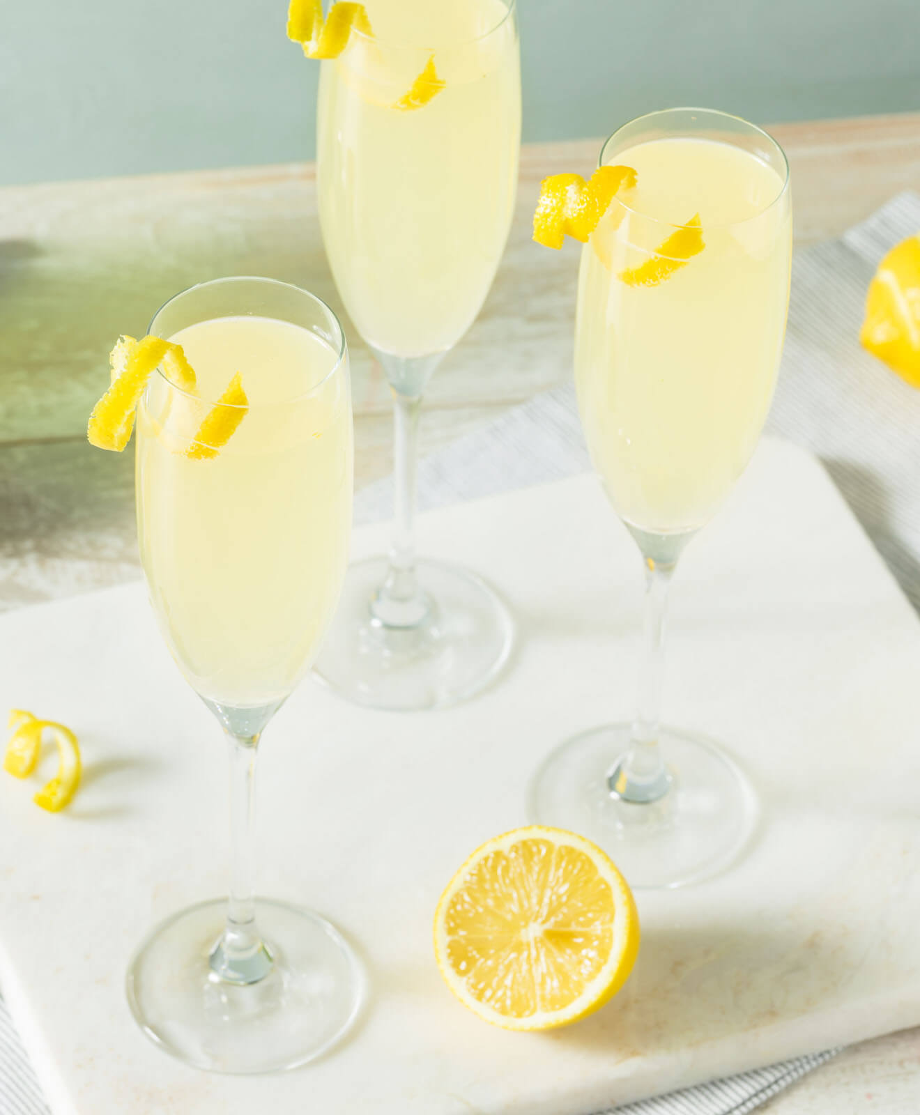 French 75 cocktails, with lemon garnish, tray and lemons