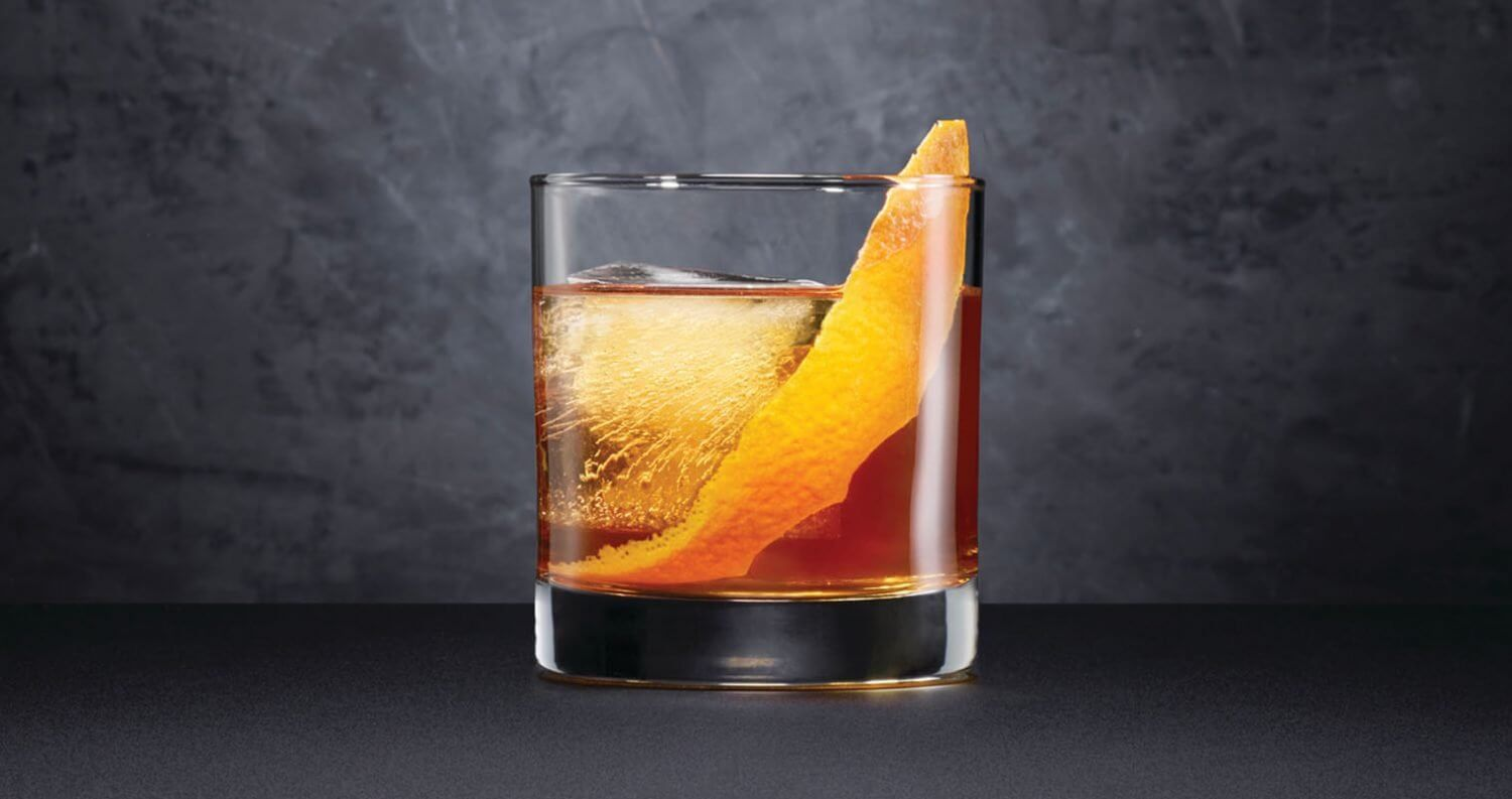 Black Barrel Old Fashioned, cocktail with garnish, dark grey background, featured image
