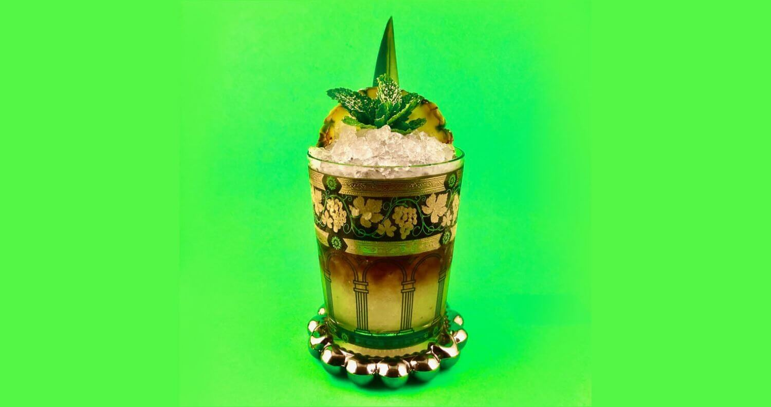 Trick Pot Cobbler, garnished cocktail, green background, featured image