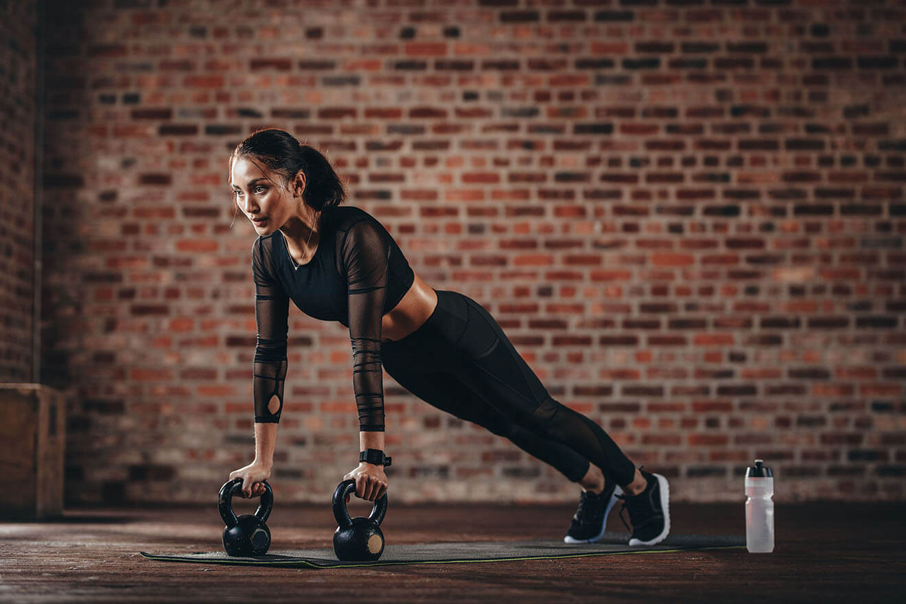 fitness girl doing planks, brick wall background