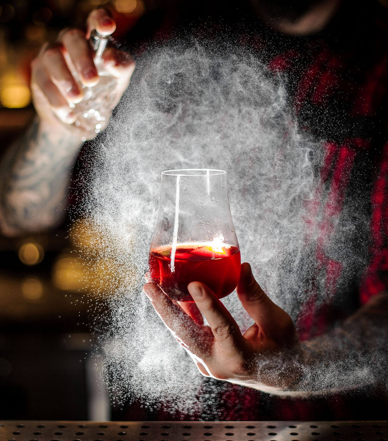 bartender spraying a sazerac cocktail