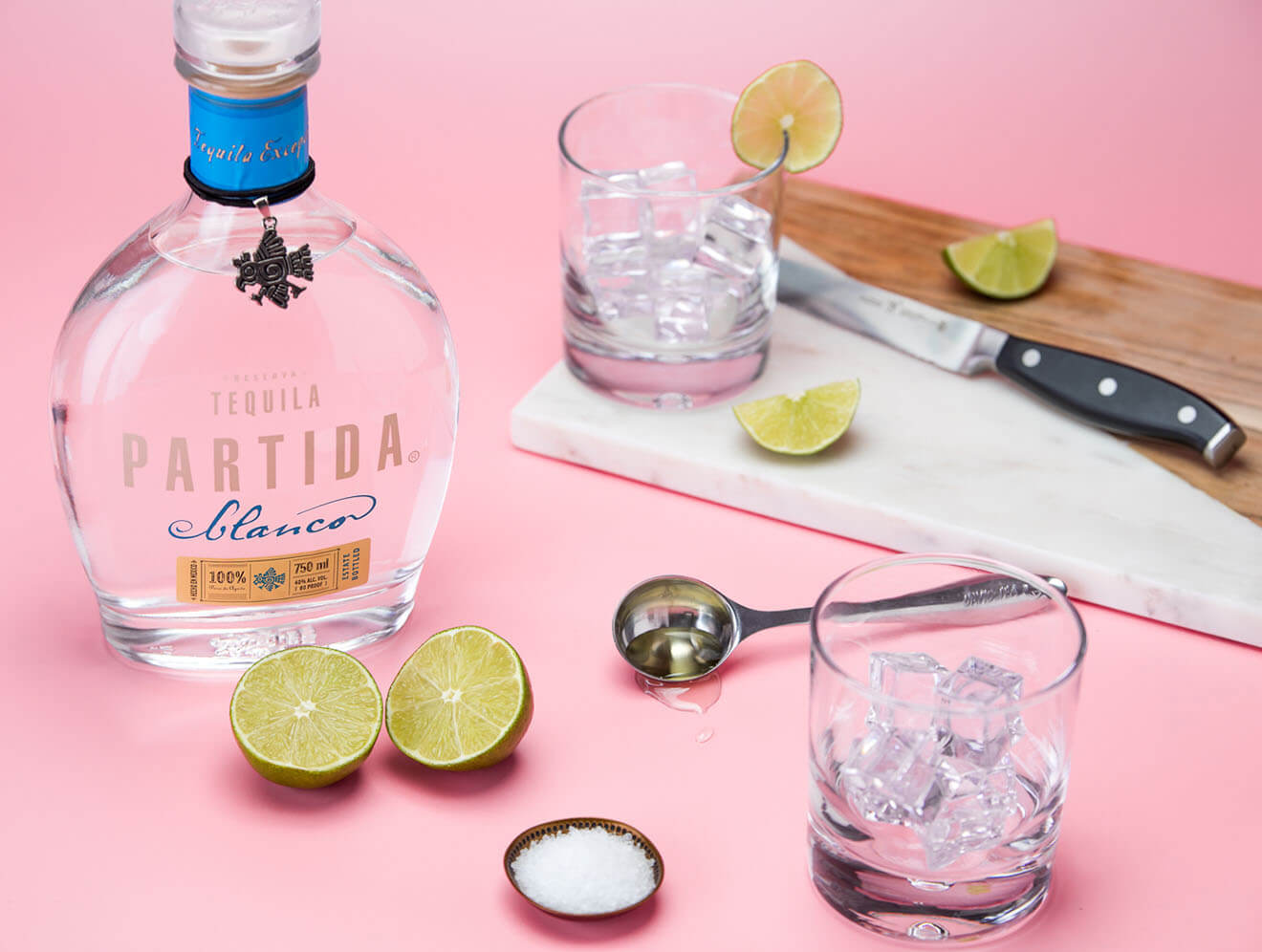 Partida Tequila, bottle, garnishes and bar tools, pink background