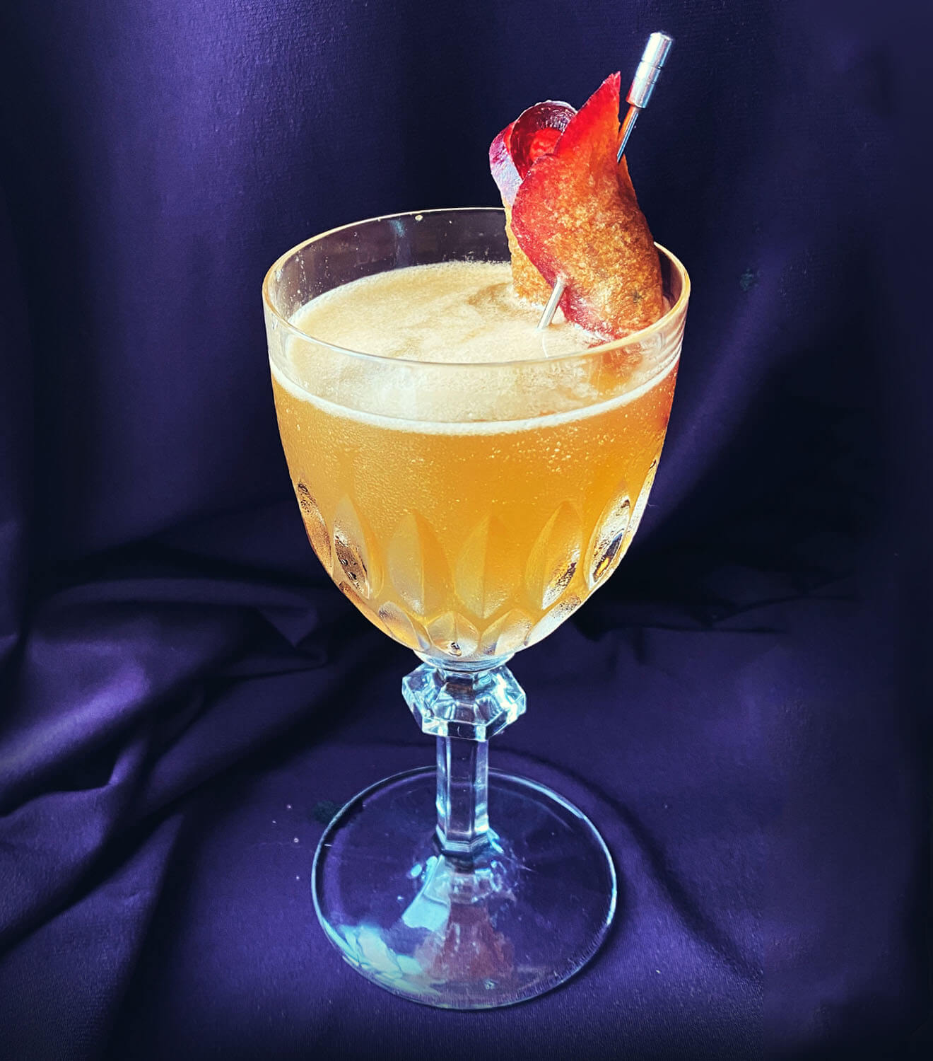 Plum's the Word, cocktail with garnish, blue velvet back