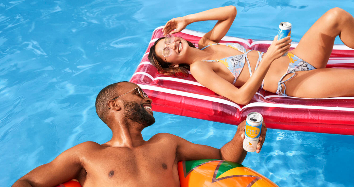 enjoy high noon, man and woman in floats on pool, featured image