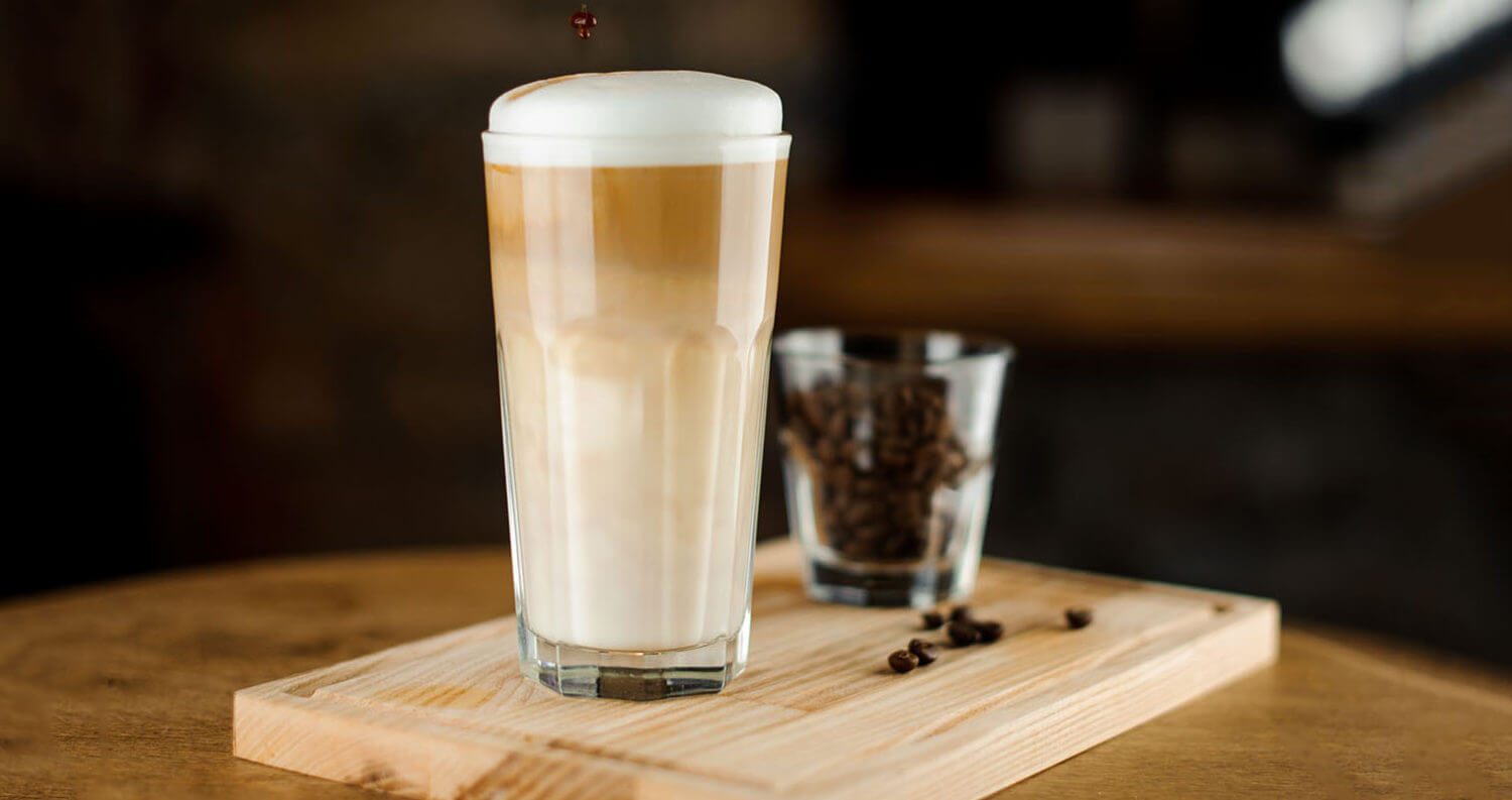 Hot coffee latte in a high glass glass on a wooden board. Glass of coffee beans in the background