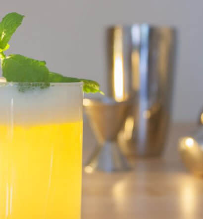 A fresh drink with mint garnish with stainless steel shaker, jigger and top., featured image